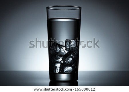Glass of water filled with ice cubes backlighted - stock photo