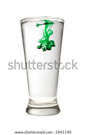 Glass of water isolated on white with green color dye spreading inside. - stock photo