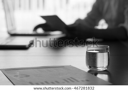 glass of water on conference table in conference room with black and white tone.