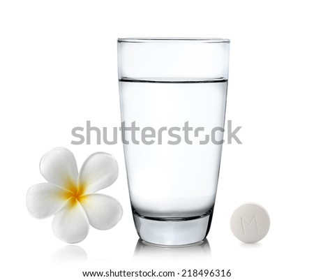Glass of water pills and frangipani flower isolated white background - stock photo