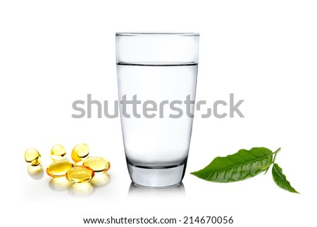 Glass of water wiith green tea leaf and fish oil isolated on white background - stock photo