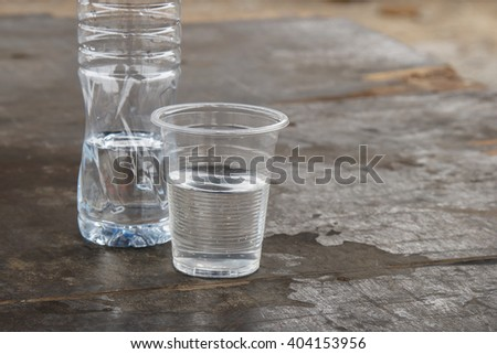 glass of water with bottle on a table in natural. - stock photo