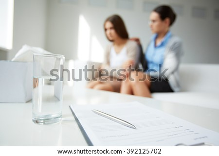 Glass of water with documents on table with people in the background