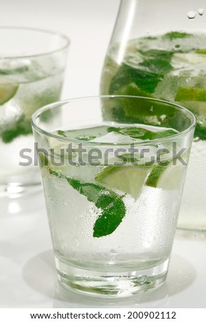 Glass of water with ice cubes, mint and lime s