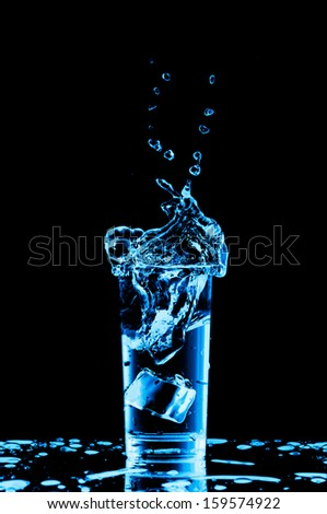 Glass of water with ice cubes on black background. - stock photo