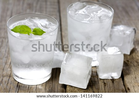 Glass of water with ice cubes on vintage wooden planks - stock photo