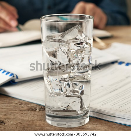 glass of water with ice on a wooden office desk. Against the background of a glass of water running man. Copy space. Free space for text. Square frame - stock photo