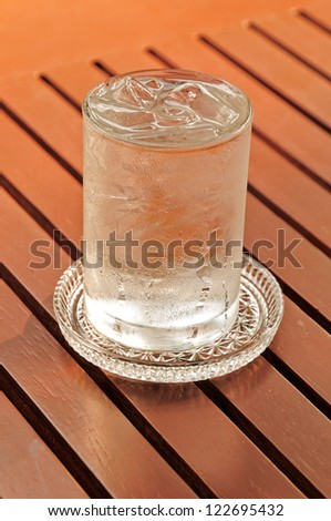 glass of water with ice on red wooden table. - stock photo