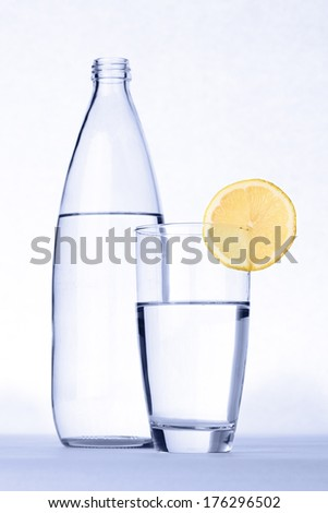 Glass of water with lemon in front of water bottle isolated on white.