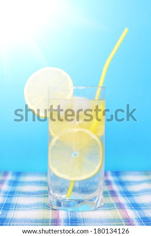 Glass of water with lemon on a blue background - stock photo