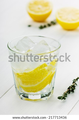 glass of water with lemons and ice cube on a white board - stock photo