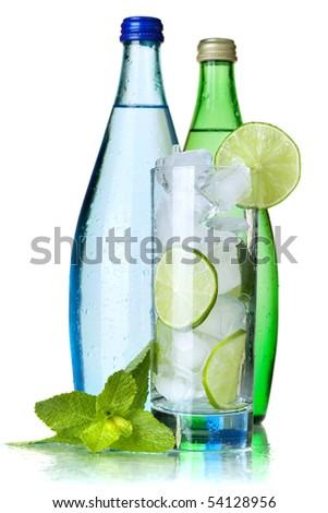 Glass of water with lime and ice, two bottles with mineral water. Isolated on white background. - stock photo
