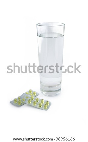 glass of water with the pills on a white background - stock photo