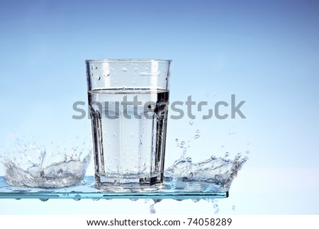 Glass of water with water splashes an a glass surface / panel - stock photo