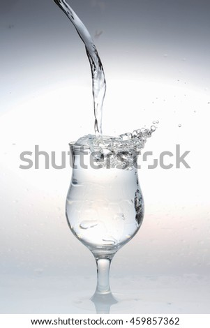 Glass of water with water splashes and wet on white background