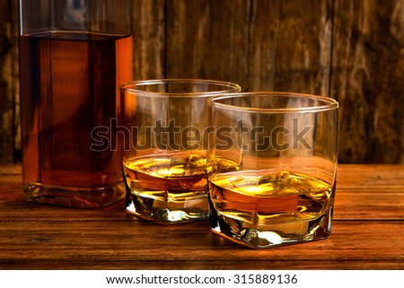 glass of whiskey  and bottle on a wooden background. - stock photo