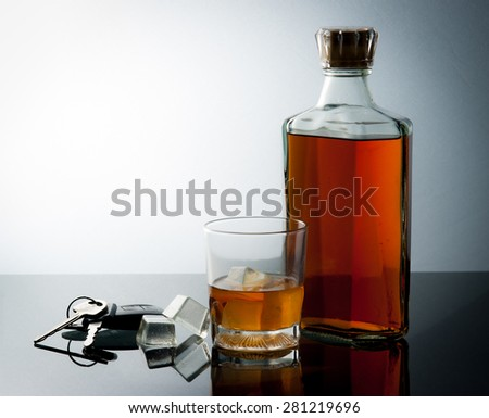 Glass of whiskey and car keys on gradient background