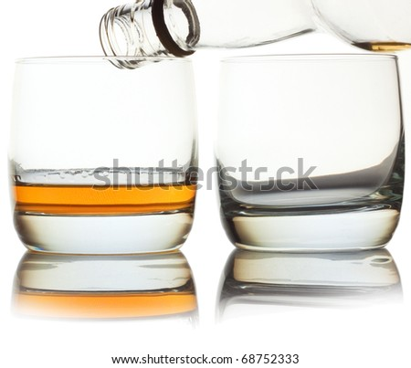 Glass of whiskey and empty glass with bottle - stock photo