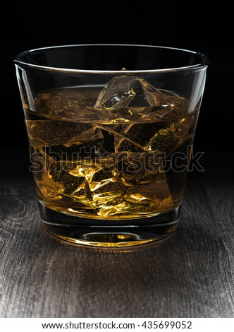 Glass of  whiskey and ice on a wooden table - stock photo