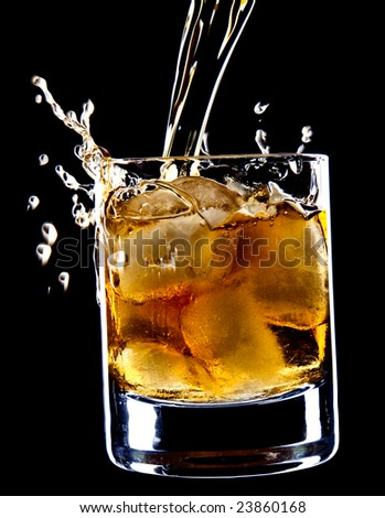 glass of whiskey and ice under the pouring whiskey isolated over black background - stock photo