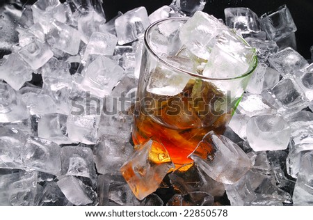 glass of whiskey on a ice cubes. square crystal