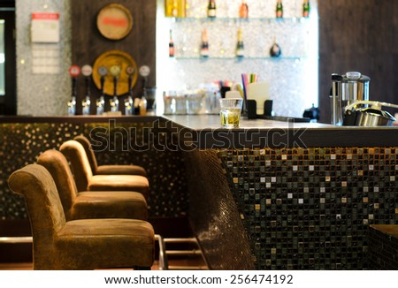 Glass of whiskey on a wooden counter in a bar or nightclub with empty chairs and a blurred man visible in the background - stock photo