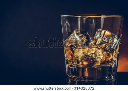 glass of whiskey on black background with reflection, warm atmosphere, time of relax with whisky with space for text