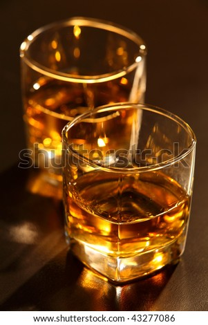 Glass of whiskey on brown bar counter - stock photo