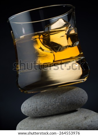 Glass of whiskey on the rocks standing on a pile of stones - stock photo