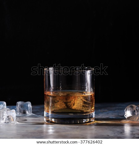 Glass of whiskey on the rocks  with some ice on the table. Concept of hard liquor. Square - stock photo