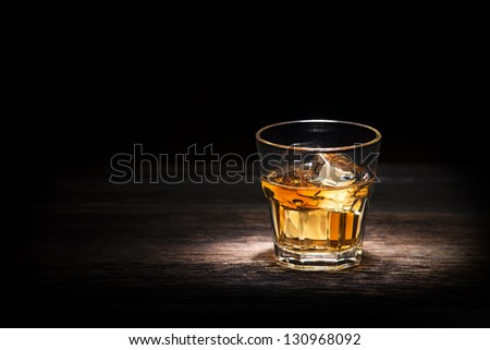 Glass of whiskey on wooden background close up - stock photo