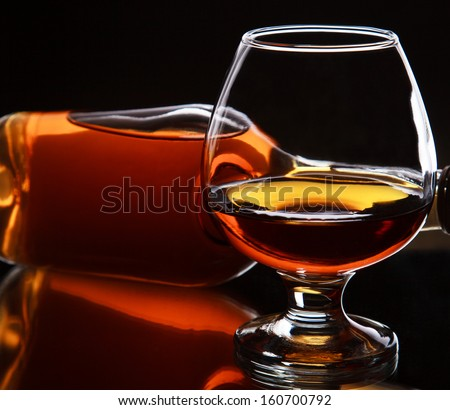 Glass of whiskey with bottle, on dark background, selective focus on the whiskey in glass - stock photo