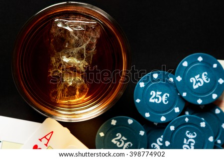 Glass of whiskey with cards and poker chips viewed from above. Horizontal image.