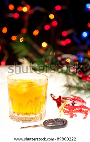 Glass of whiskey with ice, a car key and a toy car over a reindeer with lights at the background - stock photo