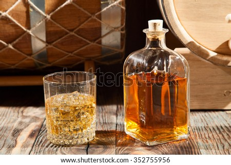 Glass of whiskey with ice and a bottle on a wooden table - stock photo