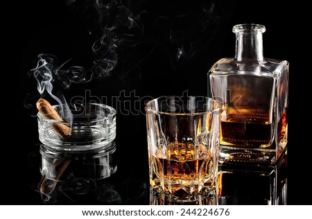 Glass of whiskey with ice, and a carafe of steaming cigar on black table - stock photo