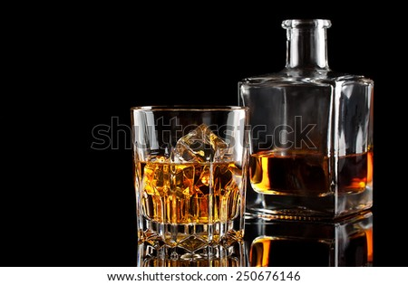 Glass of whiskey with ice and a square decanter isolated on a black background - stock photo