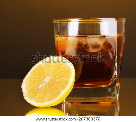 Glass of whiskey with ice and lemon on yellow background - stock photo