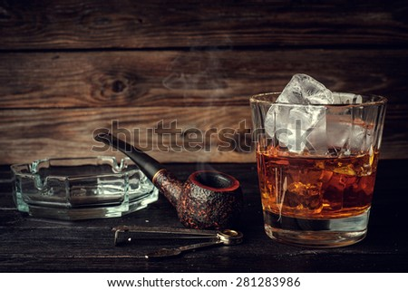 Glass of whiskey with ice and pipe on a wooden background. Vintage toned. - stock photo