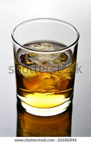 Glass of whiskey with ice close up - stock photo