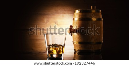 glass of whiskey with ice cubes and barrel in front of wooden background - stock photo