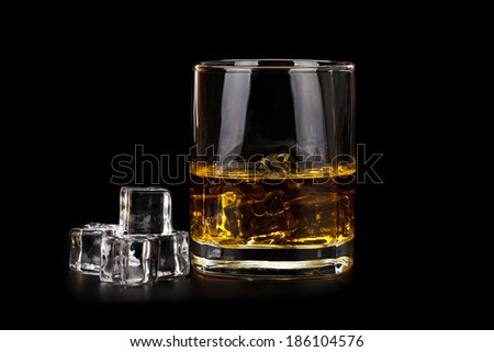 Glass of whiskey with ice cubes isolated on black background - stock photo