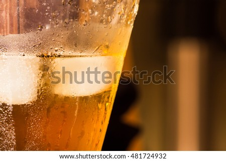 Glass of whiskey with ice cubes  on blurred background. Close up