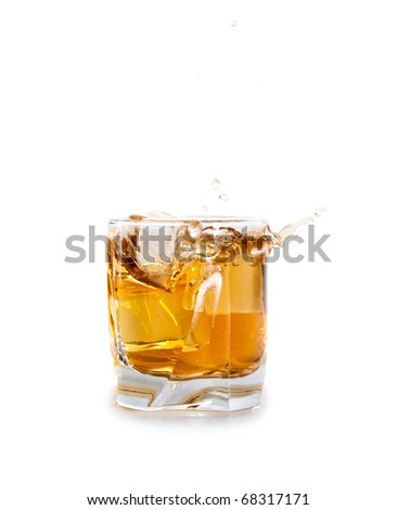 glass of whiskey with ice cubes splashing out over white - stock photo
