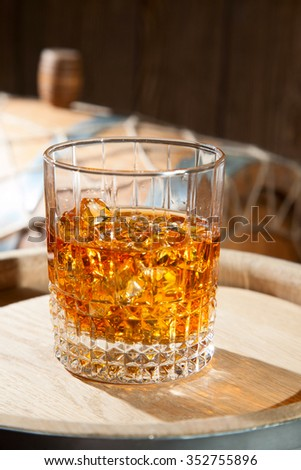 Glass of whiskey with ice on a barrel