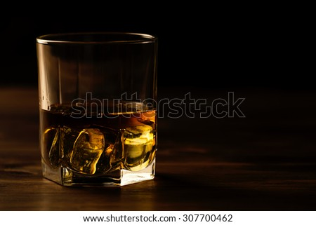 glass of whiskey with ice on a wooden table. Cognac, brandy. - stock photo
