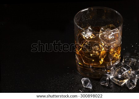 Glass of whiskey with ice on black stone table with copy space - stock photo