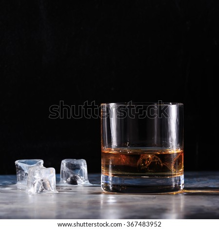 Glass of whiskey with ice on the table. Concept of hard liquor. Square - stock photo