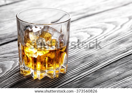 Glass of whiskey with ice on wooden surface