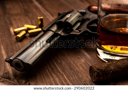Glass of whiskey with revolver and cuban cigar on the wooden table. Close up view, focus on the cuban cigar - stock photo